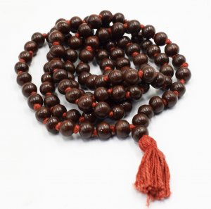 """This is a zoom-in picture of a """"MALA"""" of dark red sandalwood(LAL CHANDAN) and, each bead of red sandalwood placed on a plain white background."""