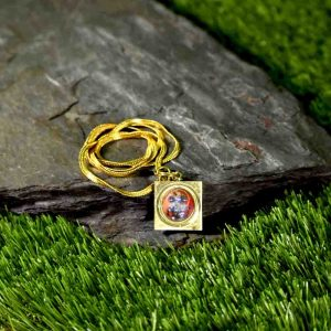The square Panchmukhi Hanuman Kavach locket with a golden chain is placed on a stone in the middle of green grass as shown in this image.