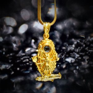 Square kali kavach locket with a golden chain hanging over a black background as shown in this image