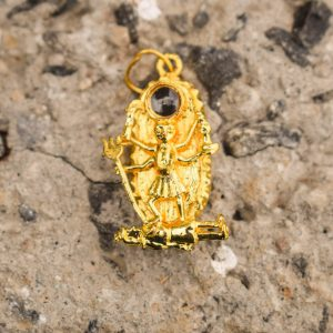 kali Kavach locket with golden chain placed on beech stone as shown in this image