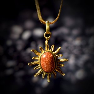 A square Surya Kavach locket with a golden chain hanging over a black stone as shown in the image